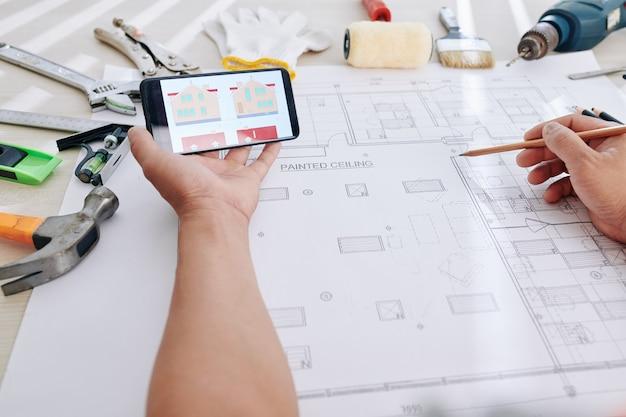 Designer confrontando l'immagine della casa con il progetto Foto Premium