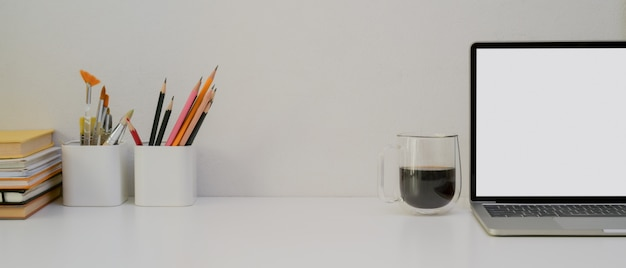 Tavolo da lavoro di design con copia spazio, laptop, cancelleria, strumenti di pittura, libri e tazza di caffè Foto Premium