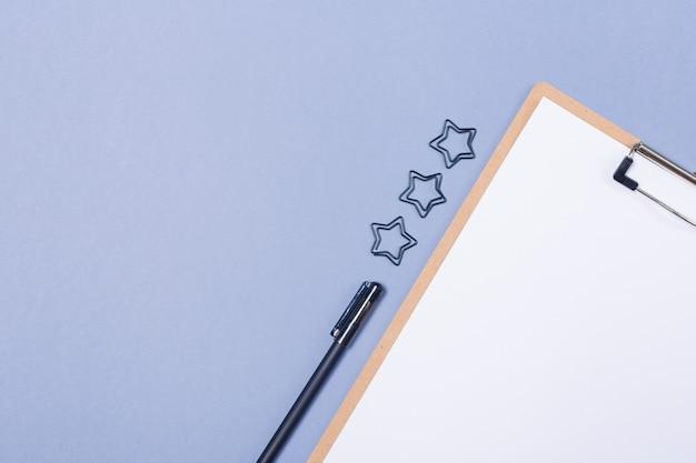 Composizione minima da tavolo con appunti in bianco, penna sul tavolo grigio chiaro, disposizione piana, vista dall'alto. copia spazio. spazio libero. Foto Premium