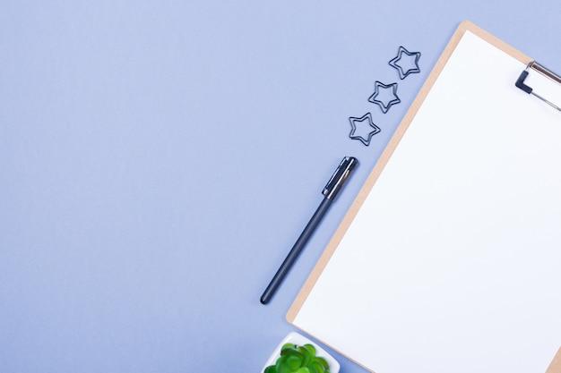 Scrivania composizione minima con appunti in bianco, penna, piccola pianta sul tavolo grigio chiaro, piatto laico, mock up, vista dall'alto. modello. copia spazio. spazio libero. Foto Premium