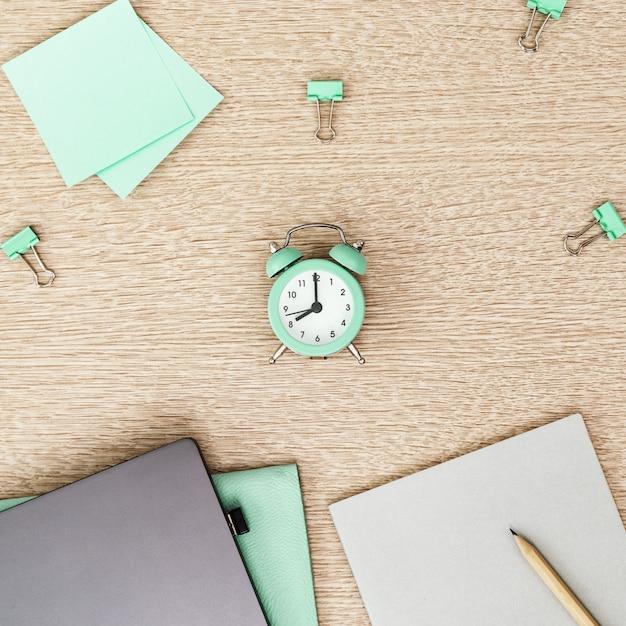Desktop per studente o libero professionista. spazio di lavoro. posto di lavoro con il computer portatile, il quaderno e l'orologio moderni grigi per controllo di tempo sul tavolo luminoso. disteso. Foto Premium
