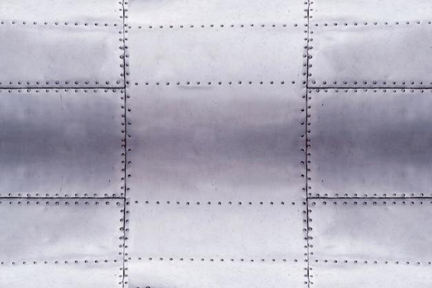 Dettaglio del vecchio pezzo di lerciume di piastra metallica con bulloni, sfondo di superficie in alluminio Foto Premium