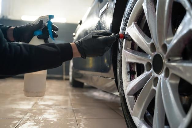 L'operatore del centro di dettagli pulisce le ruote dell'auto con la spazzola. Foto Premium
