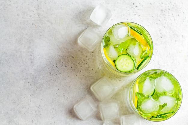 Detox sassy acqua con cetriolo e limone in vetro, sfondo chiaro, vista dall'alto. concetto di mangiare sano. Foto Premium