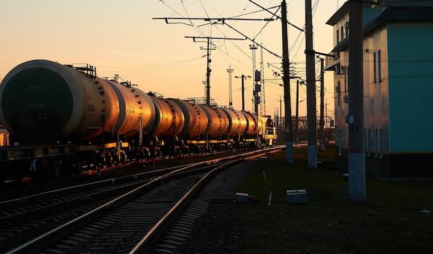 Locomotiva diesel con vagoni alla stazione ferroviaria nella luce dell'alba del mattino Foto Premium