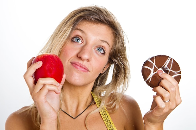 Concetto di dieta: donna nei guai tra mela o ciambelle Foto Premium