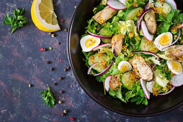 Insalata dietetica con cozze, uova di quaglia, cetrioli, ravanello e lattuga. cibo salutare. insalata di mare. vista dall'alto. disteso. Foto Premium