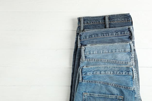 I jeans differenti hanno piegato su un fondo di legno bianco, spazio per testo Foto Premium