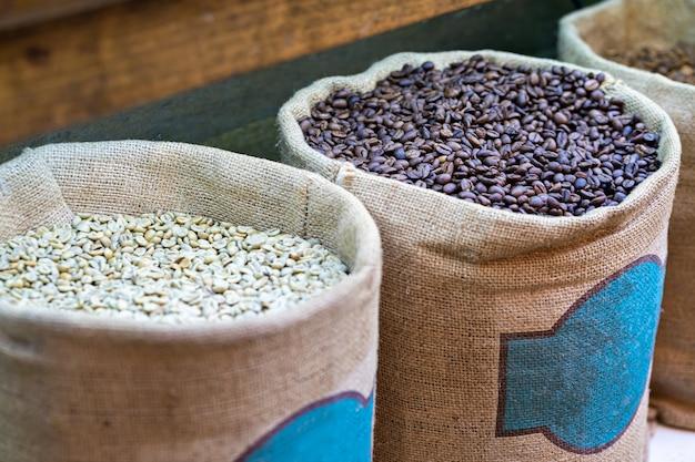 Diversi tipi di chicchi di caffè freschi in grandi sacchi di iuta al mercato Foto Premium