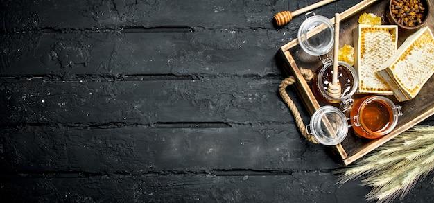 Diversi tipi di miele sul vassoio in legno. su un rustico nero. Foto Premium