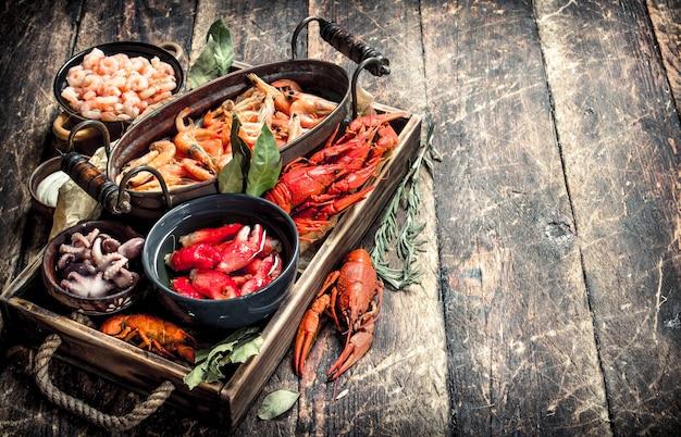 Diversi frutti di mare in ciotole. su uno sfondo di legno. Foto Premium