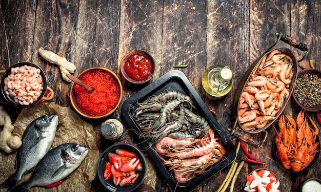 Diversi frutti di mare con gamberi e caviale rosso. su uno sfondo di legno. Foto Premium