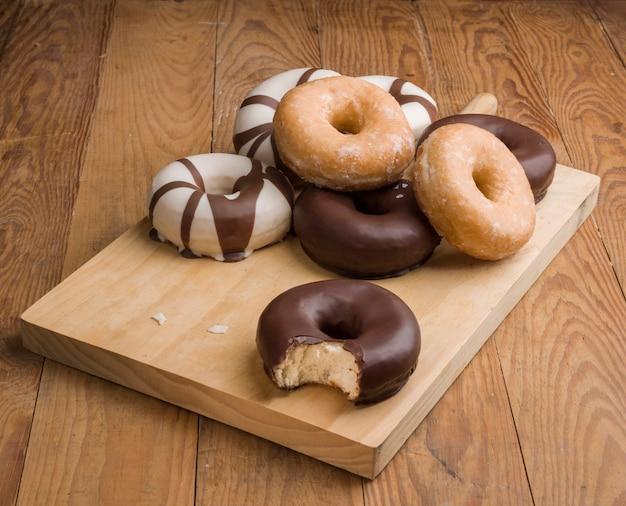Diversi tipi di ciambelle sul tavolo di legno Foto Premium