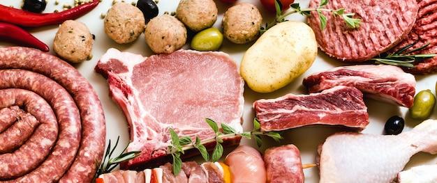 Diversi tipi di rabanner di diversi tipi di carne cruda: cosce di pollo, hamburger di maiale e manzo, costolette e spiedini, polpette di tacchino, pronte per essere cucinate con patate, Foto Premium