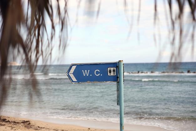 Direzione per il bagno sulla spiaggia. iscrizione del wc sulla toilette dell'insegna che appende su un palo Foto Premium