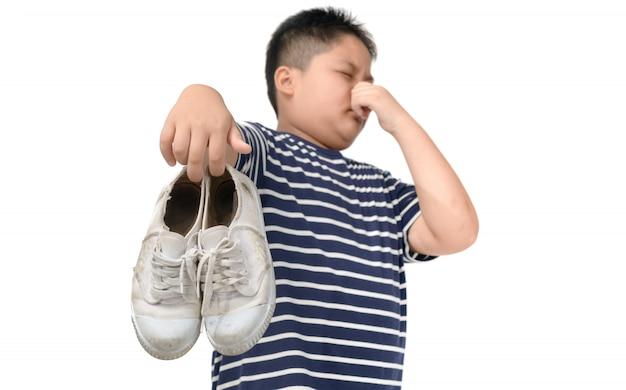 Ragazzo grasso disgustato che tiene un paio di scarpe puzzolenti Foto Premium
