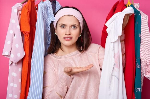 La femmina dispiaciuta mostra la camicia bianca, insoddisfatta delle dimensioni. la ragazza sta ai vestiti sui ganci nel guardaroba. la signora scontenta vuole la stessa camicetta in diversi colori. concetto di shopping e moda. Foto Premium