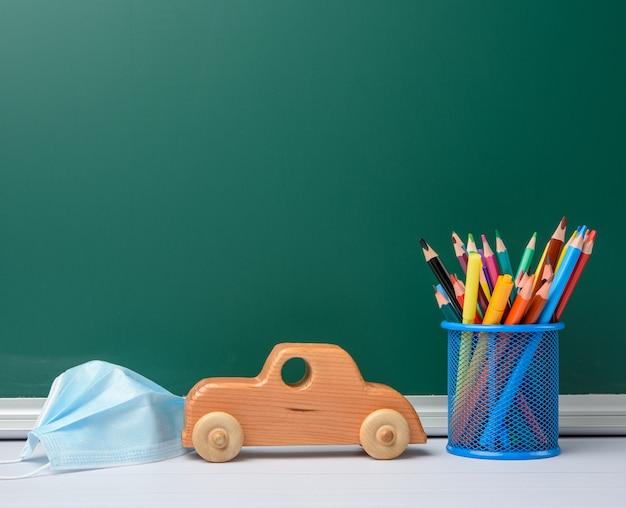 Maschera medica usa e getta, cancelleria scolastica su sfondo verde lavagna, concetto di quarantena scolastica, spazio di copia Foto Premium