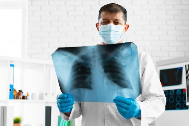 Medico che esamina la scansione a raggi x dei polmoni nel suo ufficio in ospedale si chiuda Foto Premium