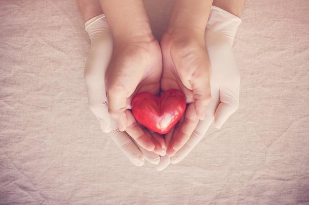 Mani del medico con i guanti che tengono le mani del bambino, cuore rosso, assicurazione sanitaria, concetto di donazione Foto Premium