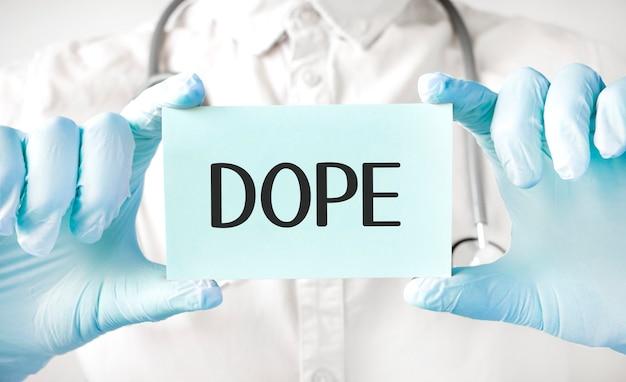 Medico che tiene la carta nelle mani e indica la parola dope Foto Premium