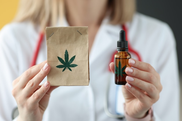 Medico che tiene il pacchetto di marijuana e olio closeup. concetto di trattamento farmacologico Foto Premium