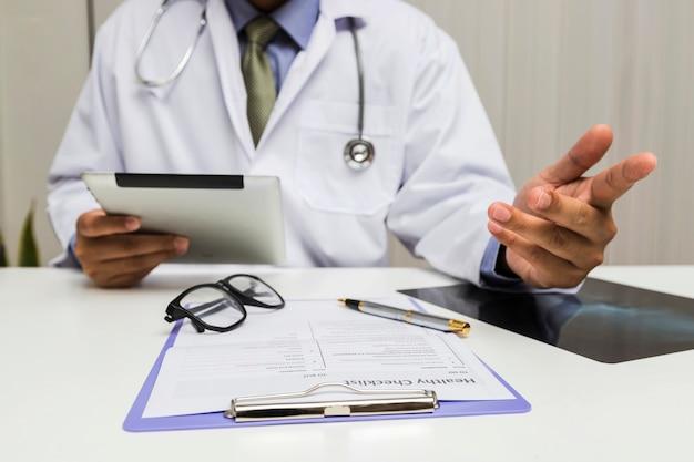 Un medico che tiene una compressa e consulta il paziente in ufficio. Foto Premium