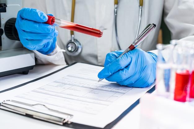 Un medico in un laboratorio detiene una provetta con un esame del sangue dei pazienti. concetto: analisi del sangue per infezione o parametri biochimici. Foto Premium