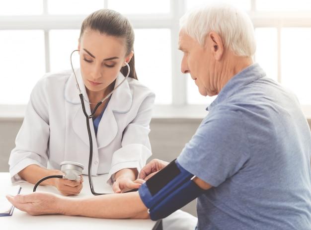 Il medico in camice medico sta testando la pressione sanguigna del paziente. Foto Premium