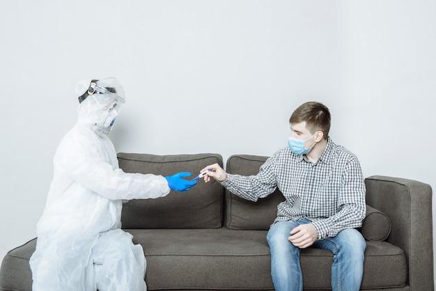 Un medico in tuta protettiva ppe hazmat che indossa una maschera e occhiali dà un termometro a un paziente Foto Premium