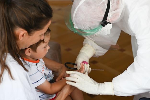 Un medico in una tuta protettiva esegue un esame del sangue da un bambino a casa Foto Premium