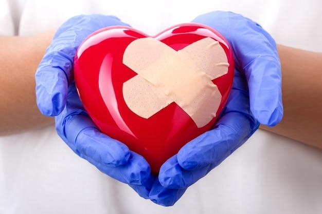 Mani del medico in guanti blu che tengono cuore intonacato Foto Premium
