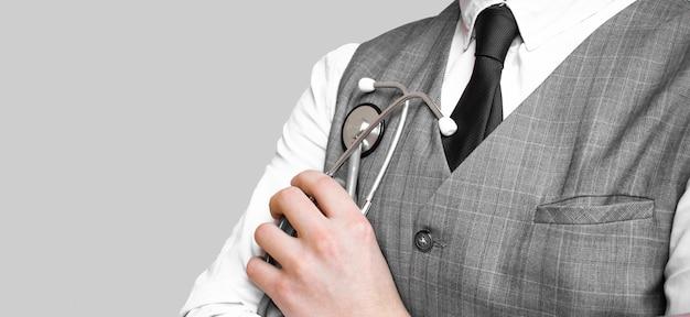 Medico in vestito che tiene uno stetoscopio grigio Foto Premium