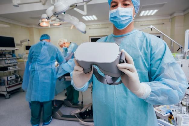 Dottore in una sala chirurgica con occhiali per realtà virtuale sullo sfondo dell'operazione reale. Foto Premium