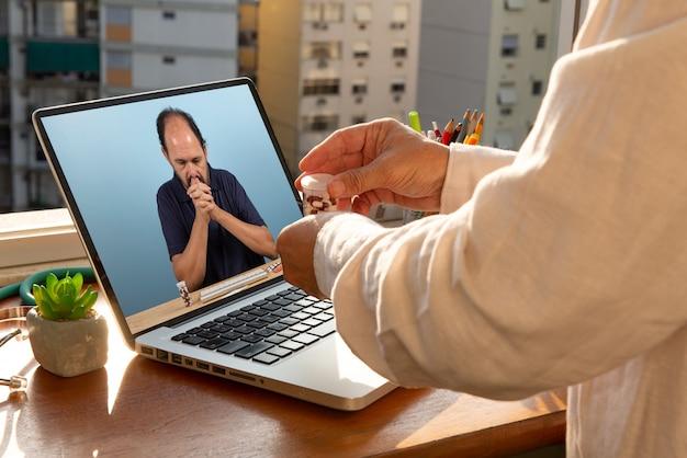 Il medico parla con il suo paziente tramite telemedicina durante la pandemia di coronavirus nel suo ufficio davanti alla finestra. il paziente è alla disperata ricerca di covid-19 Foto Premium