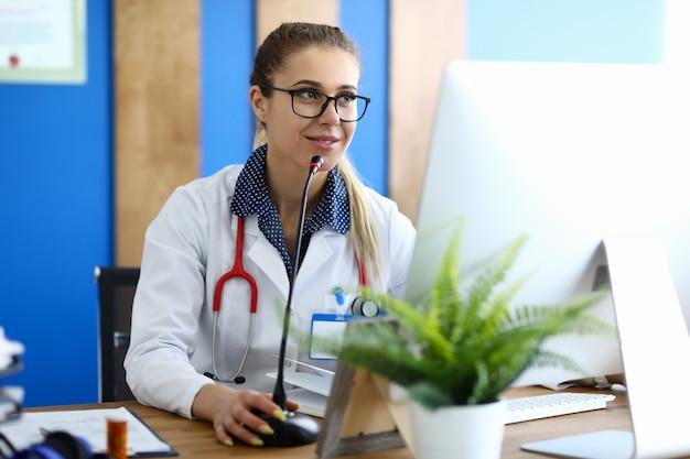 Il dottore in camice bianco offre una consulenza online tramite computer Foto Premium