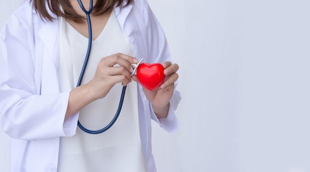 Medico con stetoscopio esaminando il cuore rosso Foto Premium