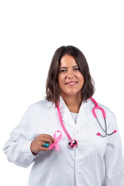 Medico donna con stetoscopio rosa che tiene il cancro al seno nastro rosa su sfondo bianco. Foto Premium