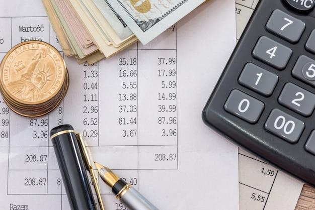 Fatture del dollaro con documenti aziendali, penna e calcolatrice come sfondo. Foto Premium