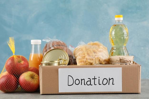 Scatola di donazione con cibo diverso sul tavolo grigio. volontariato Foto Premium