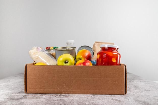 Scatola di donazione con cibo naturale sano, frutta, cereali e conserve su un tavolo grigio Foto Premium