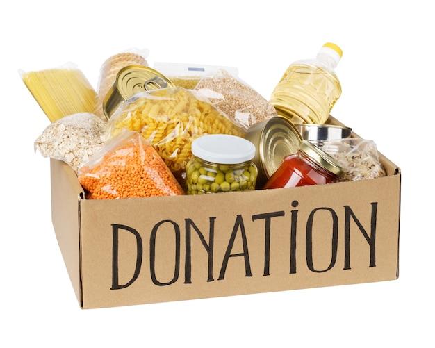 Scatola per donazioni con vari alimenti. scatola di cartone aperta con olio, cibo in scatola, cereali e pasta. isolato. Foto Premium