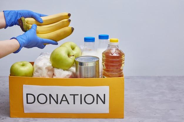 Donazione e materiale di aiuto alimentare durante la pandemia di coronavirus. le mani in guanti protettivi blu prendono o posano il cibo. Foto Premium