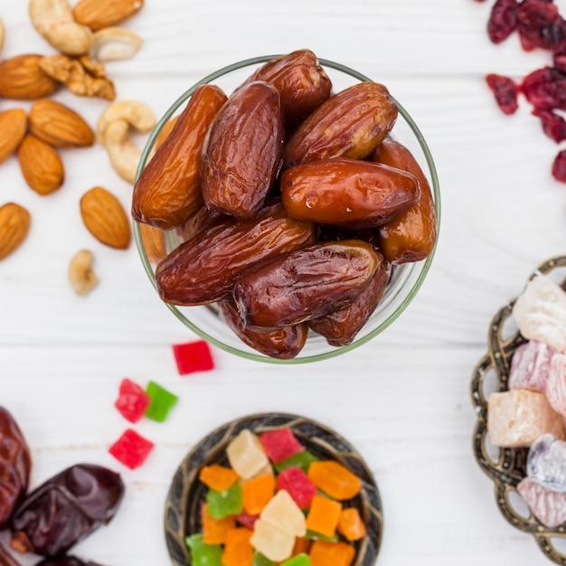 Datteri secchi frutta in una ciotola con diversi dolci Foto Premium