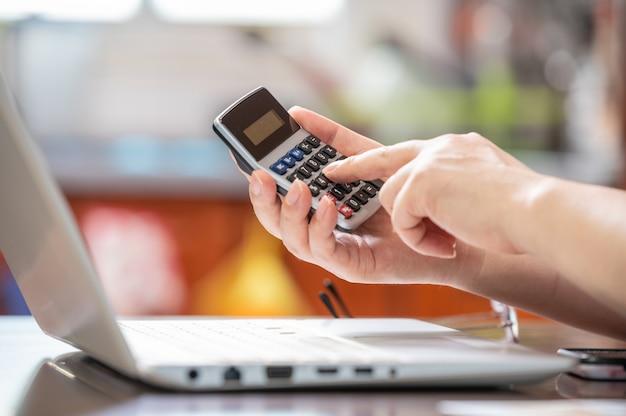 Concetto di e-commerce. la mano della persona che tiene la calcolatrice e inserisce i dati. Foto Premium