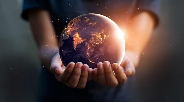 La terra di notte stava tenendo in mani umane. giorno della terra. concetto di risparmio energetico. Foto Premium