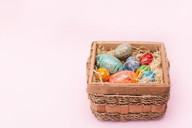 Uova di pasqua nel cestino su sfondo rosa con spazio di copia Foto Premium