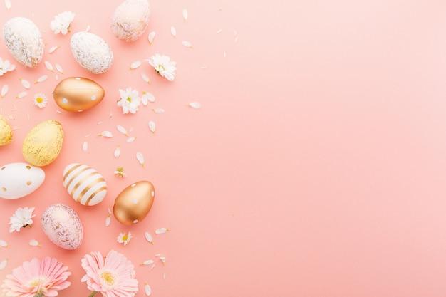 Disposizione piana di pasqua delle uova con i fiori sul rosa Foto Premium
