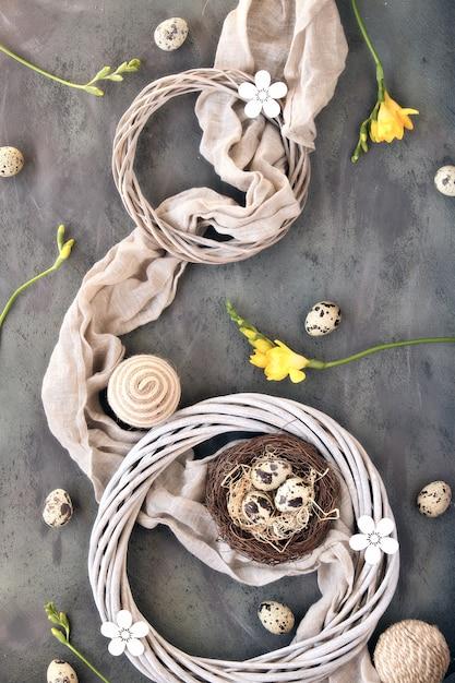 Piatto di pasqua laici, uova di quaglia e nido di uccelli su un asciugamano di lino. fiori gialli di fresia, ghirlanda di rattan. Foto Premium