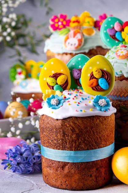 Tavola di pasqua con dolci tradizionali di pasqua, uova dipinte e rami di fiori Foto Premium